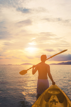 a guy pulling kayak to the sea in sunset, vacation holiday summertime concepts, vintage tone Foto de archivo
