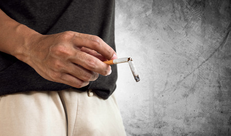 Hand holding burning break cigarette. concept of break quitting cigarette and cigarette's disease in impotence problems.cigarette issue Standard-Bild