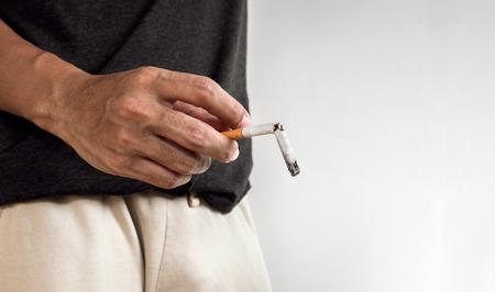 Hand holding burning break cigarette. concept of break quitting cigarette and cigarette's disease in impotence problems.cigarette issue Foto de archivo