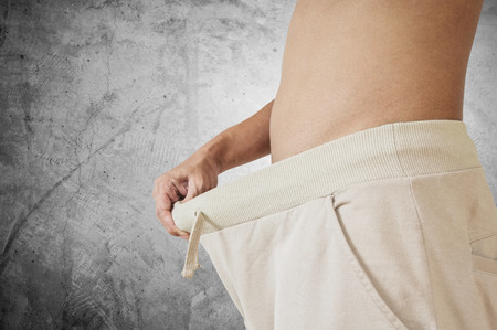 impotent: Hand pulling warm pant. diet concept. sexuality problems concept Stock Photo