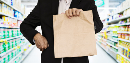 lifestyle shopping: Businessman showing brown paper bag at supermarket Stock Photo