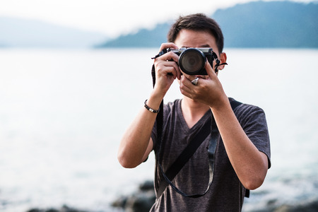 avocation: Asian guy holding camera taking a photograph