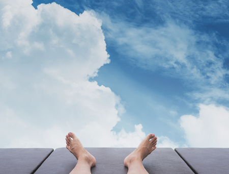 pies masculinos: Male feet relaxing on sunbathing bed, with the sky Foto de archivo