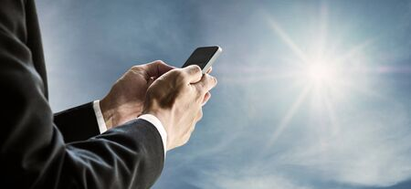 Businessman using smartphone with blue sky and sunshine background
