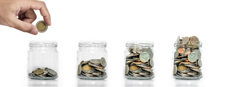 Money saving, Hand putting coin in glass jar with coins inside growing up, on white background Фото со стока