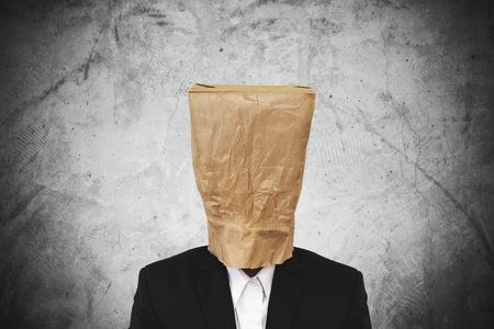 brown paper bag: Businessman with brown paper bag on head, on dark concrete texture background