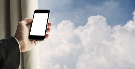 fluffy clouds: Businessman using mobile phone with curtain opened, and blue sky with fluffy clouds background