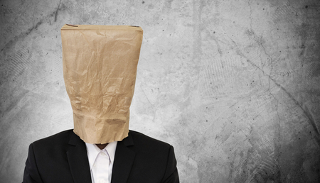 brown paper bag: Businessman with brown paper bag on head, on dark concrete texture background, with copy space