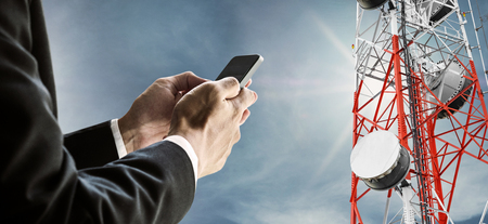 Zakenman die mobiele telefoon, met satellietschoteltelecommunicatienetwerk op telecommunicatietoren op blauwe hemel met zonneschijn, telecommunicatie in zaken en ontwikkeling met behulp van
