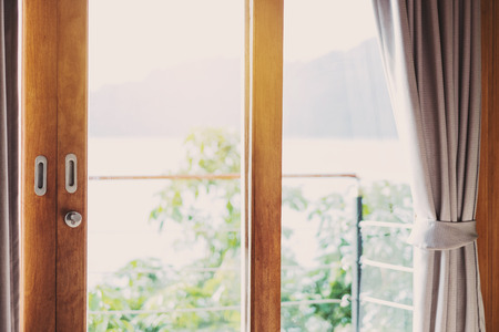 balcony door: Wooden balcony door frame with curtain in the morning, with bright light, vintage tone