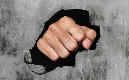 orifice: Fist breaking old dirty concrete wall