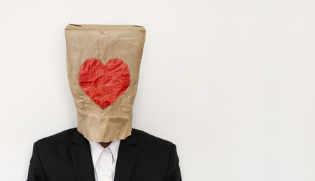 bureaucrat: a guy in suit wearing brown paper bag with heath shape Stock Photo