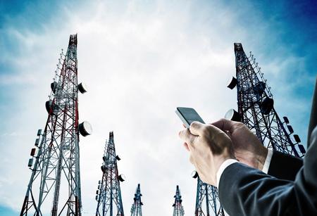 El hombre de negocios utilizando teléfono móvil con torres de telecomunicaciones con antenas de televisión y antena parabólica en el cielo azul Foto de archivo - 59399446
