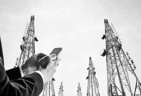 Businessman using mobile phone with Telecommunication towers with TV antennas and satellite dish, black and white Foto de archivo