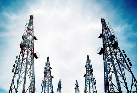 Telecommunication towers with TV antennas and satellite dish on clear blue sky Archivio Fotografico