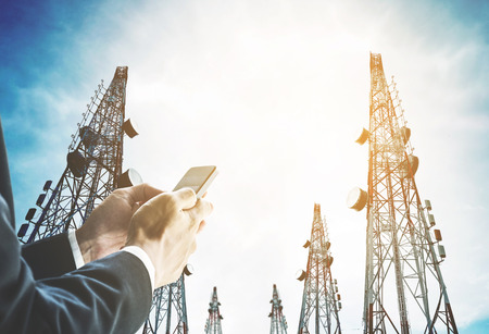 Businessman using mobile phone with Telecommunication towers with TV antennas and satellite dish in sunrise, vintage tone, soft focus