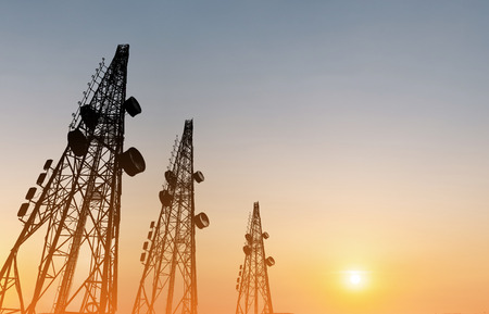 Silhouette, telecommunication towers with TV antennas and satellite dish in sunset Stok Fotoğraf