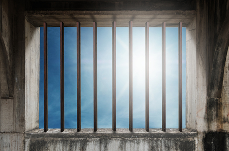 jailhouse: Old window frame with iron bar in jail, and blue sky with bright sunlight