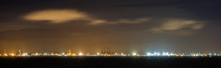 flare stack: Panorama far view of with flare stack of cargo ship and crane at port at night in Thailand Stock Photo