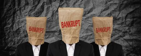bankrupt: Group of businessman, brown paper bag on head with BANKRUPT word on black crumpled texture