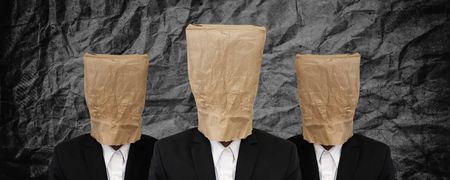 brown paper bag: Group of businessman with brown paper bag on head on black crumpled texture Stock Photo