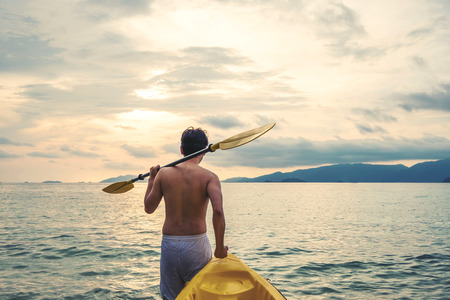kayaker: a guy pulling kayak to the sea in sunset, vacation holiday summertime concepts, vintage tone Stock Photo