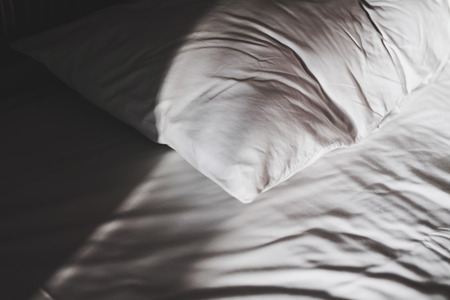 counterpane: Low key, close-up white bed wand pillow, with shade and shadow in the morning