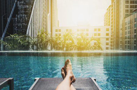 sun bathing: Relaxing in holidays, Asian guy feet on sun bathing bed at swimming pool in the city Stock Photo
