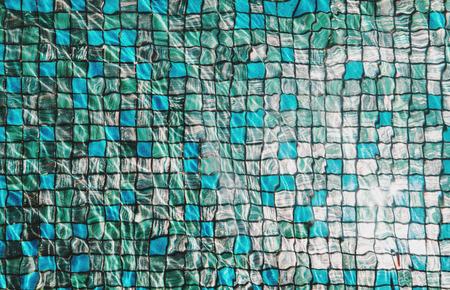 Blaue Mosaikfliesen unter Schwimmbad mit wellige Wasser und Reflexion von hellem Sonnenlicht