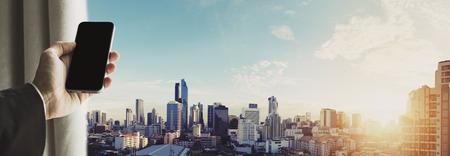 Mano que sostiene el teléfono móvil con el paisaje urbano panorámica de la ciudad de Bangkok en la salida del sol, tono de época Foto de archivo - 60143716