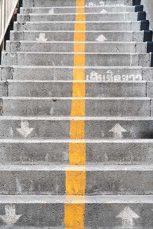 oppose: Concrete stairs with direction arrows and yellow vertical line, with Thai words on step means Walk on Right side
