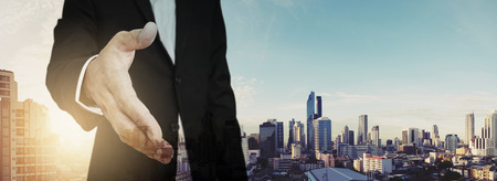extending: Businessman extending hand with panoramic cityscape of Bangkok city in sunrise, vintage tone Stock Photo