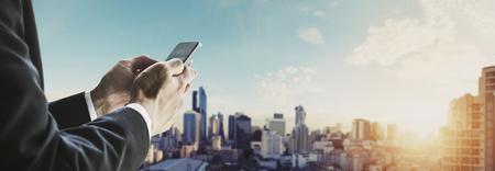 ビンテージ トーン、サンライズにバンコク市内のパノラマ景観と携帯電話を使用しての実業家