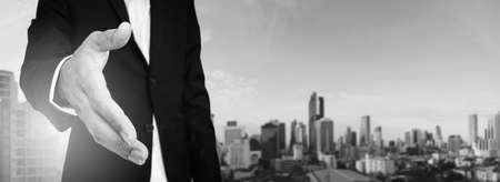 extending: Businessman extending hand with panoramic cityscape of business district in the city, black and white Stock Photo