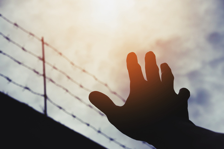 prisoner of war: Silhouette hand extending to the sky with defocus barbwire, on gloomy overcast sky with bright sunlight, vintage tone