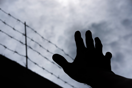 emanation: Silhouette hand extending to the sky with defocus barbwire, on gloomy overcast sky Stock Photo