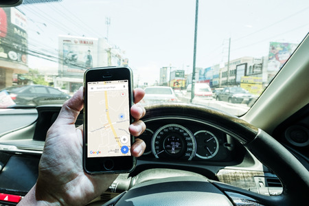THAILAND - 9 AUG - Hand using holding  iphon using Google Map application while driving on street in Thailand on August 9,2016