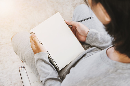 Asian guy holding blank notebook with pencil in living room, with bright sunlight, vintage tone