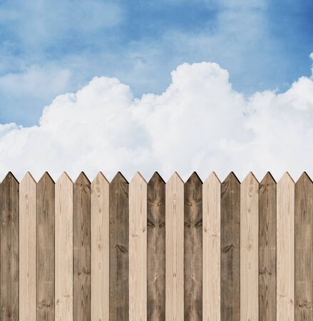 picket: Wooden picket fence with blue sky and clouds