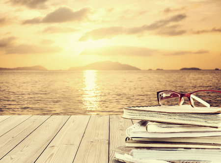 Piles of books with eye glasses on wooden desk, at tropical beach in summer in sunset, vintage tone Imagens