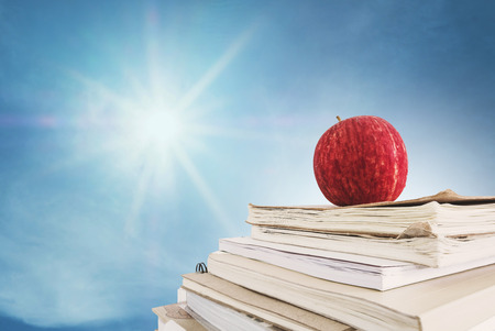 Red apple on stacked of notebooks, on blue sky with sunshine with rays