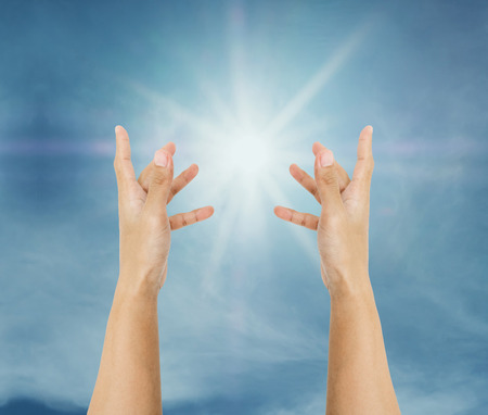 Hand trying to reach on the sky with sun rays Stock Photo
