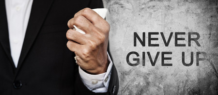 intrinsic: Businessman fist squeeze paper on concrete texture with NEVER GIVE UP word, panorama composition Stock Photo