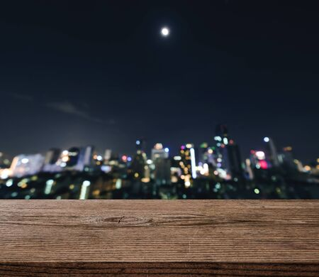 night table: Empty wooden table platform and bokeh of night urban city at night Stock Photo