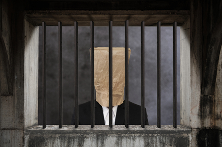 defamation: Businessman with brown paper bag on head, in jail