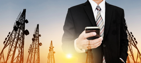 Panoramic, Businessman using mobile phone with Telecommunication towers with TV antennas and satellite dish in sunset Standard-Bild