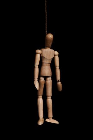 ahorcado: Bajo llave, figura de madera ahorcado con una cuerda, sobre fondo negro