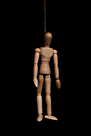 Low key, wooden figure hangman by rope, on black background