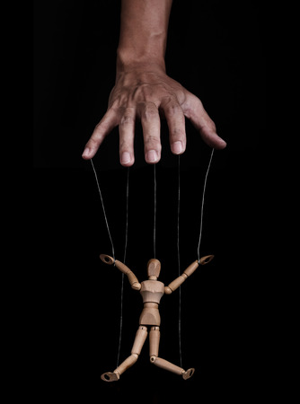 impotent: Hand controlling wooden figure, low key images, on black background