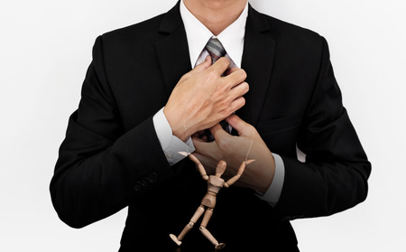 puppet master: Businessman with wooden figure puppet, concept of business manipulation
